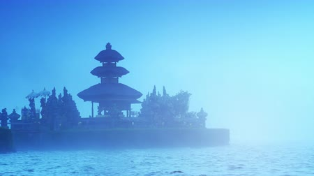 danu : Silhouette of ancient temple Ulun Danu Bratan in Bali early morning with lots of fog and mist