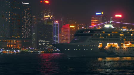 pénzügyi negyed : Huge cruise ferry in Hong Kong port at night and modern buildings of financial district on waterfront of Victoria harbor