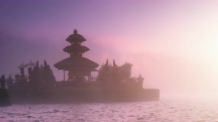 danu : Scenic background of beautiful Bali temple in mist on lake under sunset sunlight Stock Footage