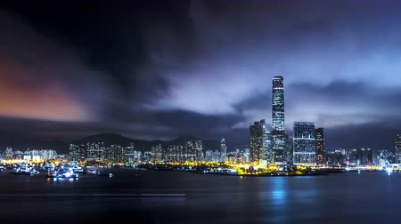 urban skyline : Night Hong Kong city skyline reflects in water of harbour. 4K urban background Stock Footage