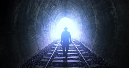 céu : Man goes by railway tracks through dark tunnel toward bright light in the end