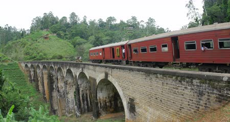 Sri Lanka train crossing old beautiful 9 Arches Bridge in Ella highlands. British architecture landmark in Asia
