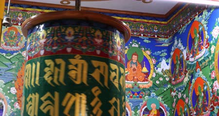 yazılı : Buddhist art and decoration in ancient temple of Ladakh. Spinning prayer wheel in monastery