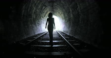 passagem : Woman entering into long dark railroad tunnel and walks inside by tracks. Conceptual psychological scene of human freedom and hope