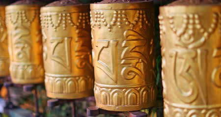 tybet : Prayer wheels in Buddhist temple in Himalaya spinning with decorated letters of mantra