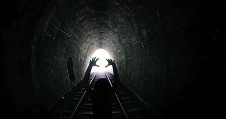 levantado : Scary human silhouette in spooky dark tunnel with light in the end. Evil female zombie attacks camera with creepy hands lifted up