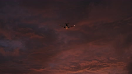 Late evening flight of airplane departing for journey trip into vivid orange sunset sky
