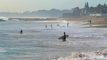 many surfers : Surfer holding the surf board entering to ocean in evening. Local people playing ball and enjoying summer time activities on sandy beach. Bali island tourist destination background Stock Footage