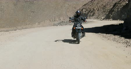 tybet : Front view of traveler riding motorcycle in mountain landscape of Ladakh region North India