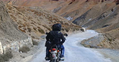 tybet : Travelers ride motorcycle on curvy road in mountain valley of Himalaya region. Ladakh in north India as tourist destination video background