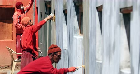 gompa : Buddhist monks in traditional red robes repair Komic monastery near Kaza in Himachal Pradeh, north India, HImalaya region