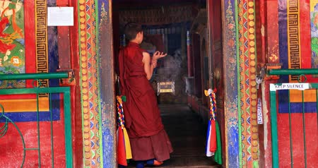 worship : Ancient Buddhist monastery Lamayuru of Bon Buddhism scene. Young monk enters inside gompa through decorated door way
