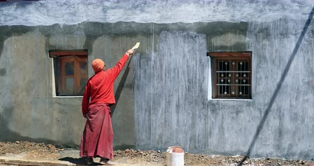 gompa : Buddhist monk applies fresh color to monastery wall in Komic gompa near Kaza in Spiti valley, northern India Stock Footage