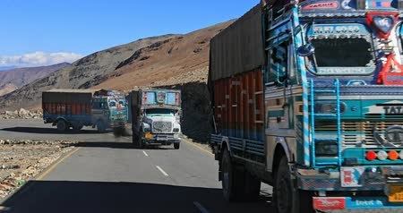 himalaia : Delivery trucks travel by curvy highland road of Manali Leh highway in Ladakh region of northern India. Traditional decoration of vehicles in Asia