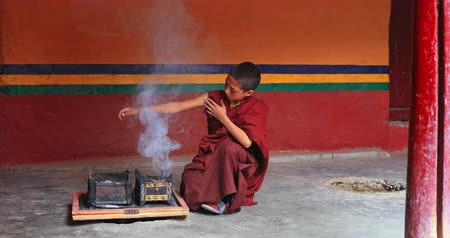 gompa : Smoke fumes raise up in Lamayuru Buddhist monastery as novice monk blows the coals. Ancient culture and traditions of Tibet and Ladakh