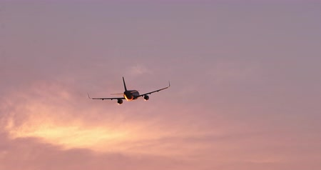 Silhouette of airplane moving on orange sunset sky flying away from camera 影像素材
