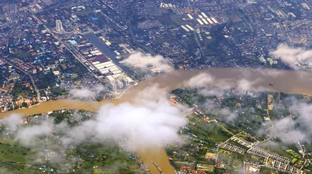 Flying above Bangkok, Thailand. Aerial view of Chao Phraya river through layer of clouds