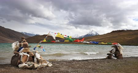 Religious buddhist prayer flags and stacking stones near Chandra Tall lake high in Himalaya mountains, northern India