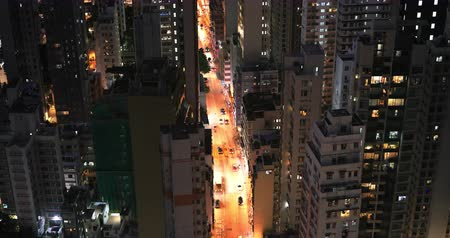 City street at night with car and apartment buildings windows lights aerial view from above downtown roofs