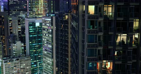 Modern city downtown at night. Apartments, condos and office buildings illumination in Hong Kong aerial view 影像素材