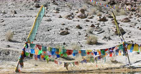 Buddhist prayer flags colorful religious decoration on Yarab Tso lake or Yereb Tso in ladakh, Jammu and Kashmir, North India, Himalaya mountains