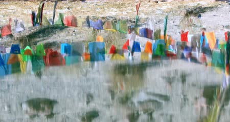 Buddhist prayer flags reflect in water. Meditation tranquil and peaceful religious background