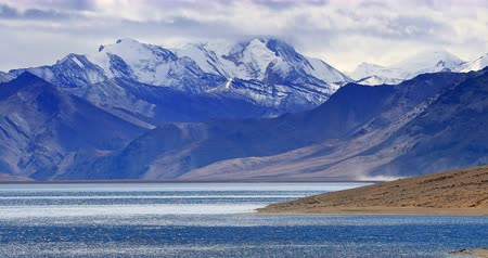 Тибет : Snow peak of Himalaya mountains range and blue water of high altitude Tso Moriri lake in Ladakh, India. Scenic nature landscape