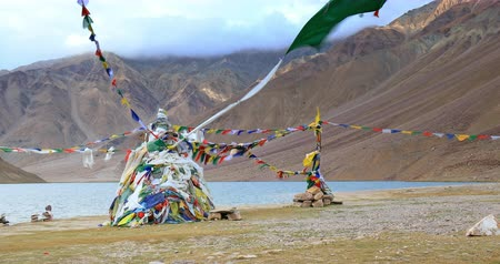 Buddhist Stupa decorated with colorful prayer flags on shore of Chandra Taal lake in Himalaya mountains, north India