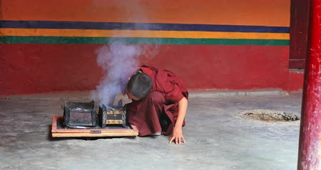 himalaia : Traveling to Himalayas of north India in Ladakh region and visiting Lamayuru ancient monastery. Young monk lights the fire and makes smoke