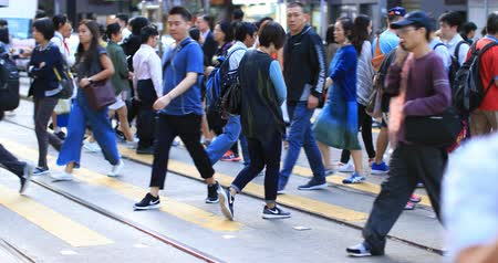daily life : Crowd of people walk on crossroad in Hong Kong city downtown. Pedestrians at rush hour time Stock Footage