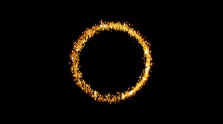 Gold glittering star dust circle of trail sparkling particles on black background.