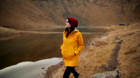 Beautiful young woman in a yellow jacket walking along the shore of a mountain lake. Girl admires the incredible view of the mountains