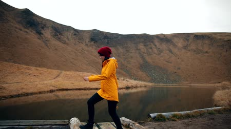 Hipster millennial young woman in yellow jacket walking along the shore of a mountain lake. Girl admires the incredible view of the mountains