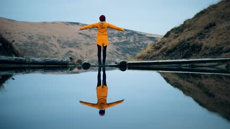 Hipster millennial young woman in yellow jacket stands on the shore of a mountain lake and raises arms into air, happy and drunk on life, youth and happiness