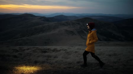 Camera follows young beautiful woman in yellow jacket and headlamp walking on top of mountain after sunset. A brilliant sunset over the mountains. High iso with Noise