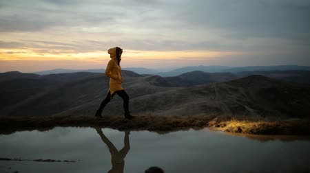 el feneri : Beautiful young woman in a yellow jacket and headlamp walking along the shore of a mountain lake on top of mountain after sunset Stok Video