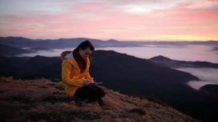 экстремальный : Digital artist girl draws nature landscape on her tablet. Woman enjoys the fresh air and freedom in the mountains. Young woman in a yellow jacket on top of a mountain enjoys an incredible sunrise