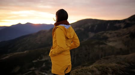 Young woman in yellow jacket stands on top of mountain and enjoys incredible sunrise. Girl enjoys beautiful mountain scenery and freedom, feels harmony and unity with nature