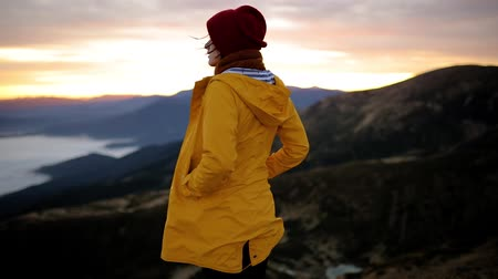 picos : Young woman in yellow jacket stands on top of mountain and enjoys incredible sunrise. Girl enjoys beautiful mountain scenery and freedom, feels harmony and unity with nature