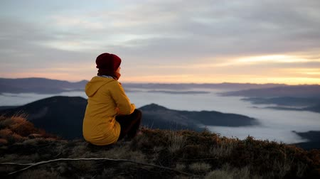 Beautiful dark-haired hiker girl sits on top of mountain and looks at scenery around. Young woman feels harmony and unity with nature