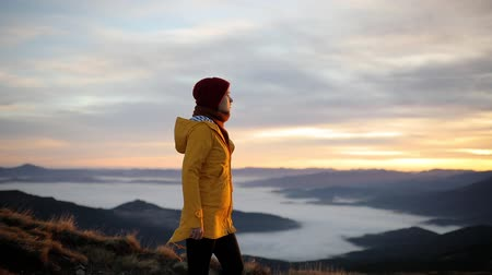 Young woman in yellow jacket walks on top of mountain and enjoys incredible sunrise. Girl happy and drunk on life, youth and happiness Stock Footage
