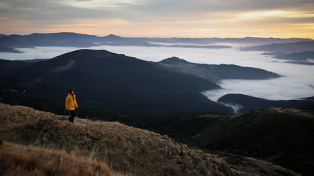 Girl in yellow jacket walks on top of mountain and enjoys incredible sunrise. Young woman feels harmony and unity with nature