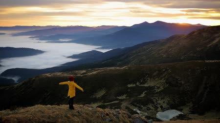Girl in yellow jacket raises her hands up to meet the sun on top of mountain and enjoys incredible sunrise. Young woman feels harmony and unity with nature Stock Footage