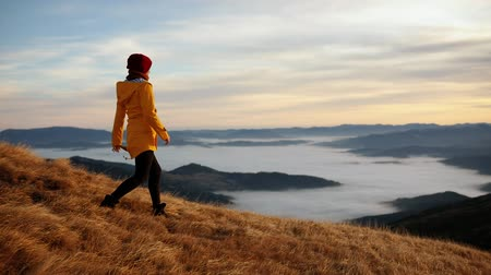 The girl in a yellow jacket comes down from the mountain and enjoys incredible views of the mountain peaks. Young woman feels harmony and unity with nature Stock Footage