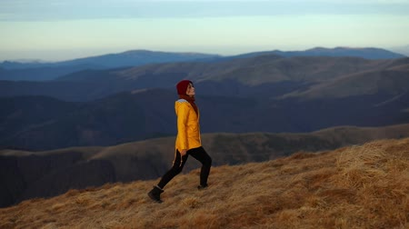 A young tourist woman in a yellow jacket climbs to the top of the mountain and enjoys the incredible views of the mountain peaks. The girl enjoys the fresh air and freedom in the mountains