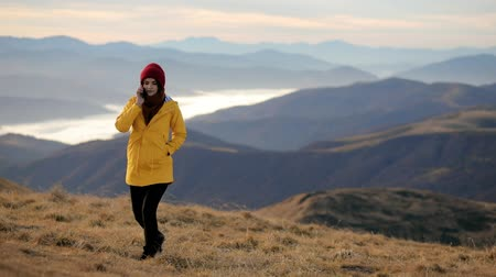 Young attractive woman in a yellow jacket on top of a mountain talking on the phone