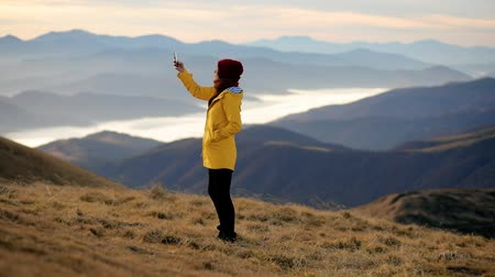 Woman trying to pick up the signal on her mobile phone in the mountains. Girl trying to use smartphone but no signal Stock Footage