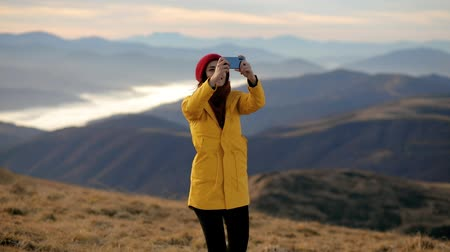 Young beautiful woman in a yellow jacket on top of a mountain takes pictures on the phone. Girl takes a panorama of mountain landscapes Stock Footage