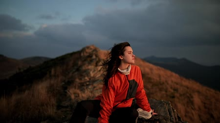 The pretty girl sits on the edge of a cliff on a mountain top and watches an incredible sunset. Young woman enjoys the windy weather, the wind flutters long dark hair