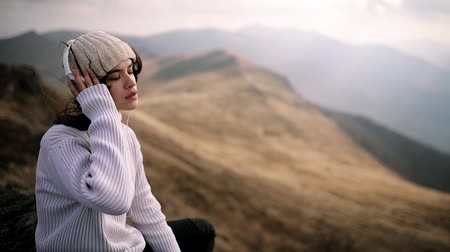Stylish girl in headphones sits on a rock on top of a mountain and listens to music. Young woman enjoys the windy weather, the wind flutters long dark hair Stock Footage